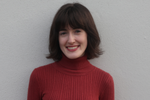 Róisín Ní Riain headshot. In the image she is wearing a red roll neck jumper and is standing against a white wall.