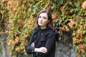 Eilish Mulholland headshot - Eilish standing cross-armed against an ivy covered wall